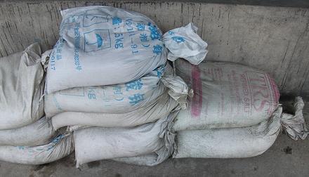 กระสอบทรายกันน้ำท่วมแบบเก่า เป็นถุงปุ๋ยบรรจุทราย มัดปากถุง